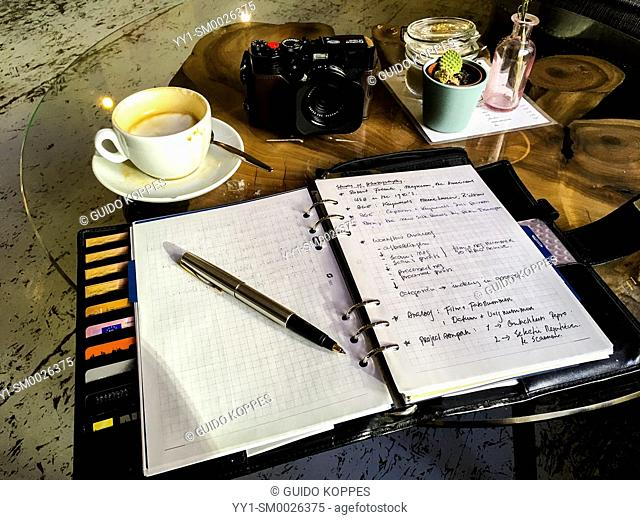 Belin, Germany. Leather, analog notebook with digital camera and cup of cappuchino on a coffeeplace's table