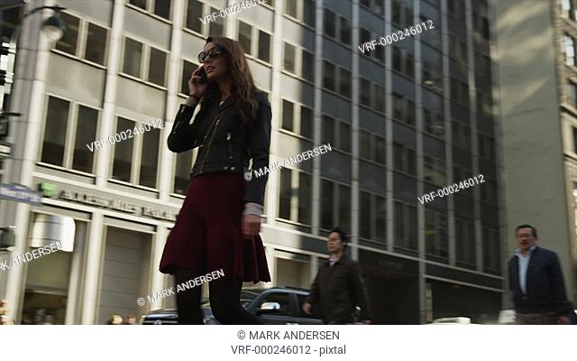 Low angle medium tracking shot of young woman talking on cell phone and walking in city / New York City, New York, United States