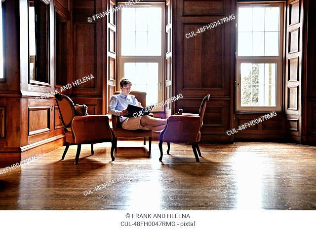 Man reading in ornate room
