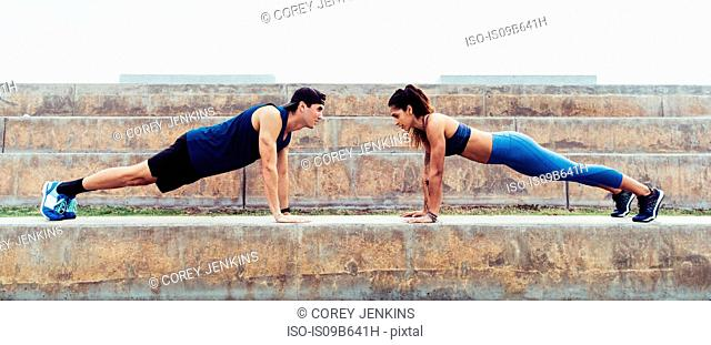 Man and woman exercising outdoors, doing push-ups on steps, South Point Park, Miami Beach, Florida, USA