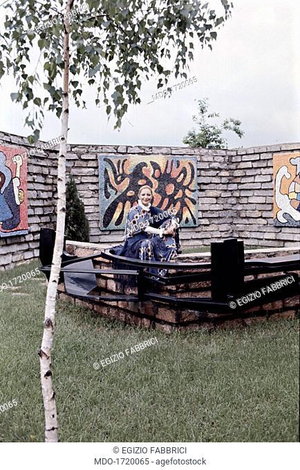 Mia Martini smiling. Italian singer Mia Martini (Domenica Rita Adriana Berté) sitting in front of some mural paintings. 1972