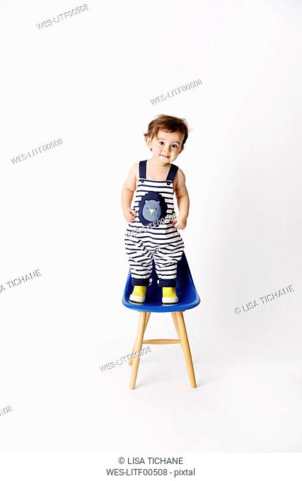 Toddler wearing striped dungarees and yellow rain boots standing on a chair in front of a white background