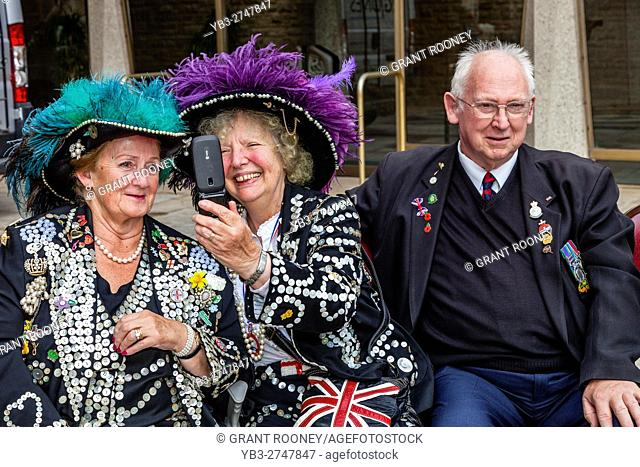 Two Pearly Queens Pose For A Selfie At The Pearly Kings and Queens' Harvest Festival, Held Annually At The Guildhall Yard, London, England