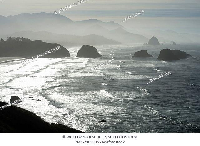 View of backlit Haystack Rock and sea stacks from Ecola State Park, located north of Cannon Beach on the Northern Oregon Coast, USA