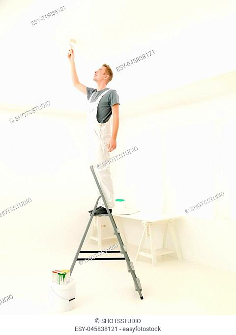 Man cheerful laughing and painting the ceiling
