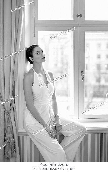 Woman sitting on window sill