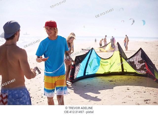 Men preparing kiteboarding kite on sunny beach