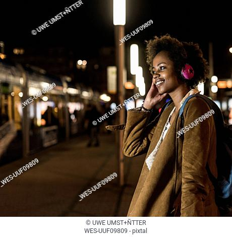 Smiling young woman listening music with headphones while waiting at the tram stop