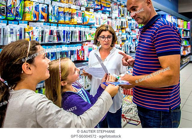 PARENTS AND CHILDREN SHOPPING AT THE SUPERMARKET BEFORE SCHOOL STARTS IN SEPTEMBER, BUYING SCHOOL SUPPLIES