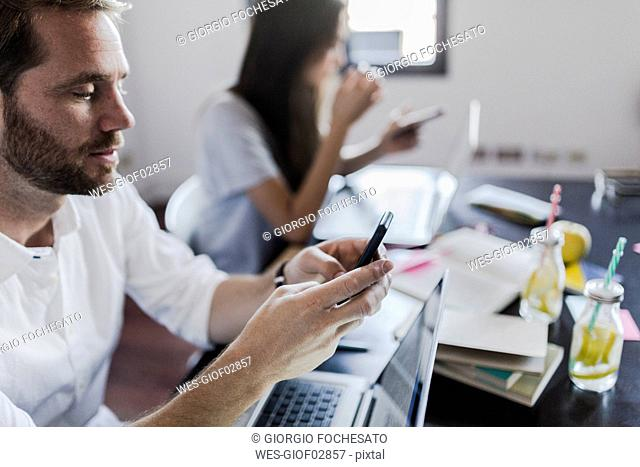 Busy couple at home using laptop and smartphone
