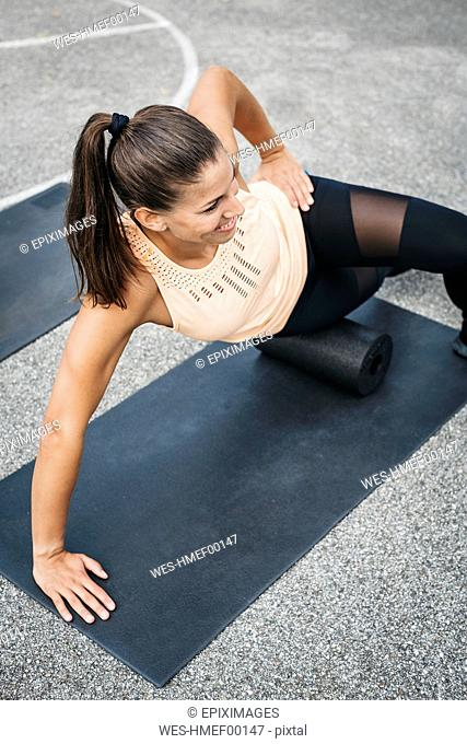 Sportive woman training with fascia roll