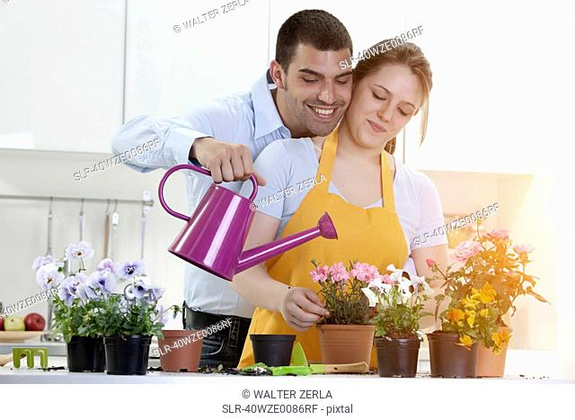 Couple watering potted plants indoors