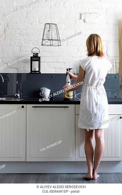 Rear view of woman using blender at kitchen counter