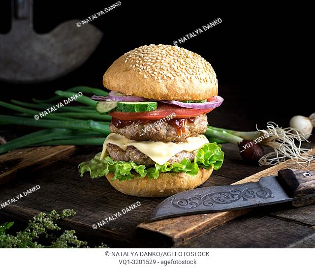 cheeseburger with vegetables on a brown old wooden board, black background