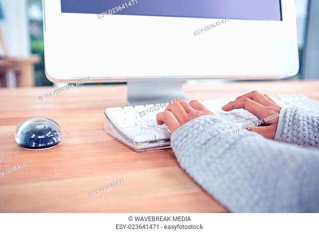 Womans hands typing on computer keyboard