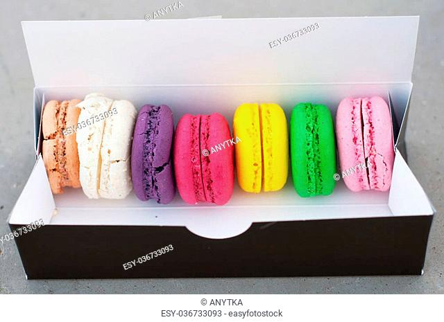 Multicolored macarons cookies in a black box