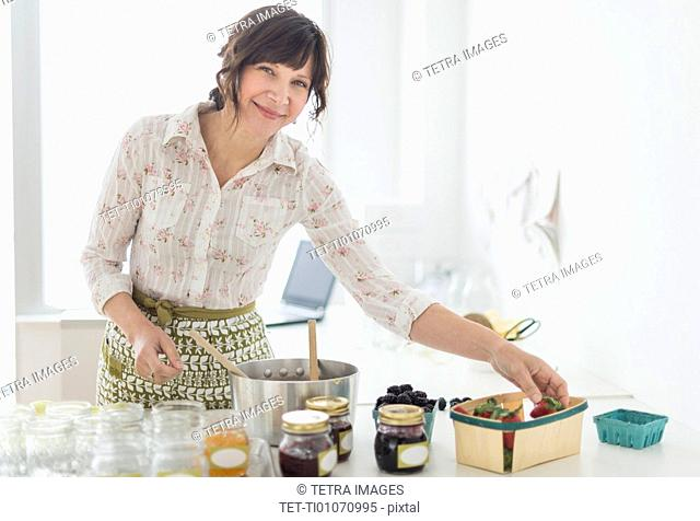 Woman making preserves in kitchen
