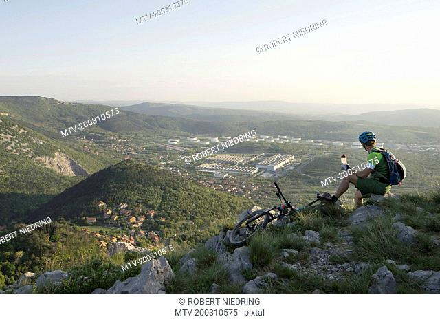 Mature biker holding water bottle in one hand while sitting on rock and looking at view