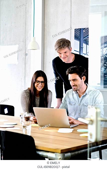 Colleagues in office using laptop smiling