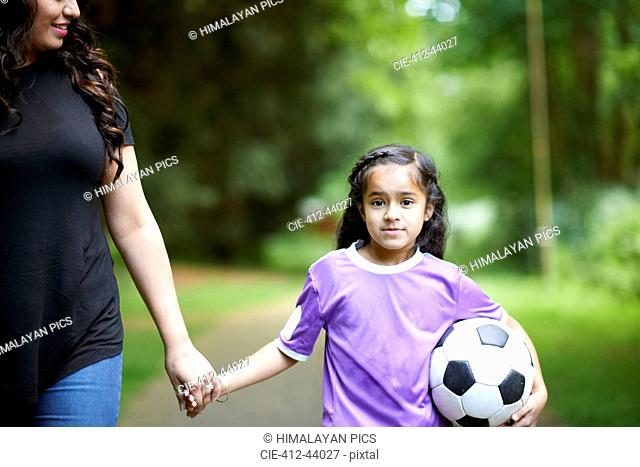 Portrait girl with soccer ball holding hands with mother