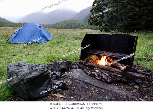 An outdoor campfire near a tent in a countryside campground. Photo by Rafael Ben-Ari/Chameleons Eye