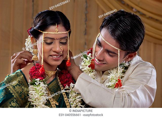 Happy young bride and groom performing marriage traditions