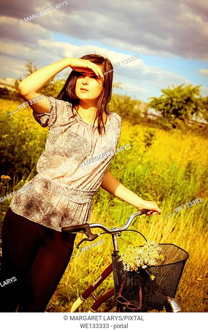 Beautiful white brunette girl with a retro bike standing in the summer fields in wonderful golden light
