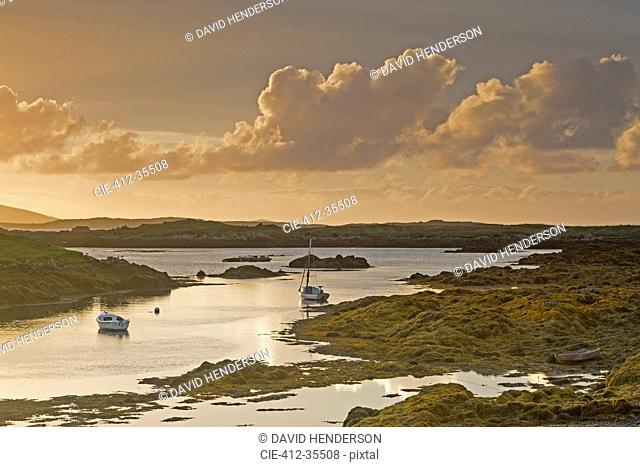 Tranquil sunset view fishing boats on lake, Harris, Outer Hebrides