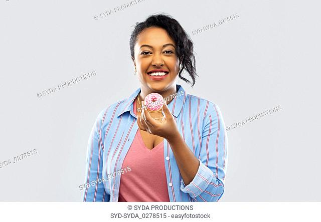 happy african american woman eating pink donut