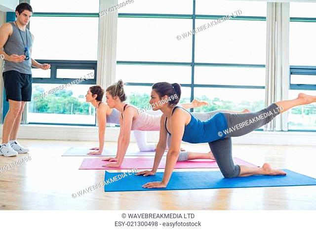 Male instructor with yoga class in the gym