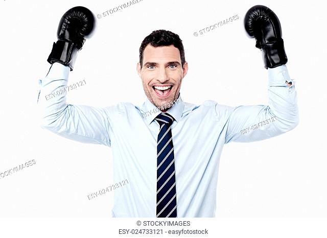 Victorious businessman raising hands with boxing gloves