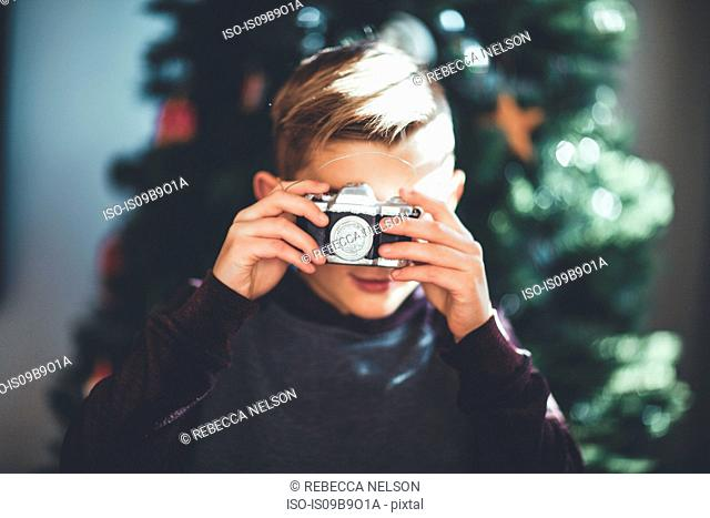 Boy taking photo, Christmas tree in background