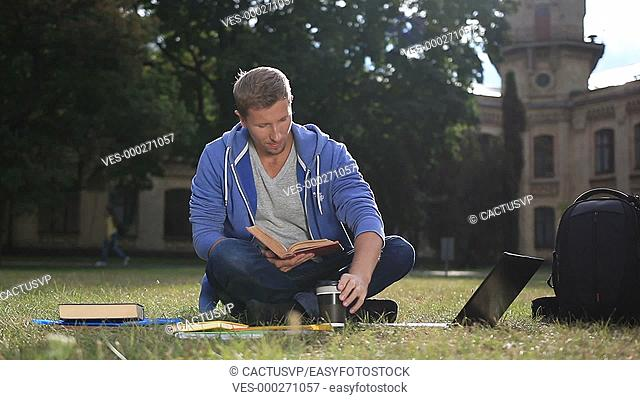 Happy young student reading a book in the park