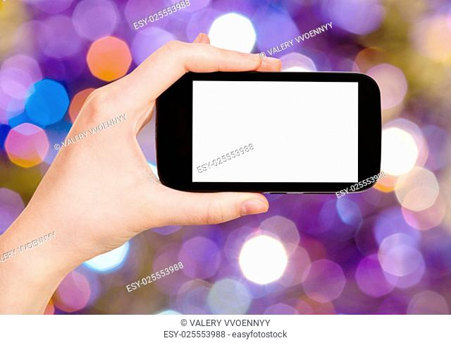 christmas party concept - hand with smartphone with cut out screen on background from dark blue and violet flickering Christmas lights of electric garlands on...
