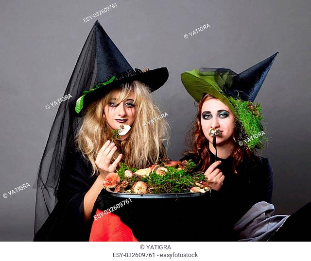 Halloween party - women in costumes of witches dine snakes and mushrooms