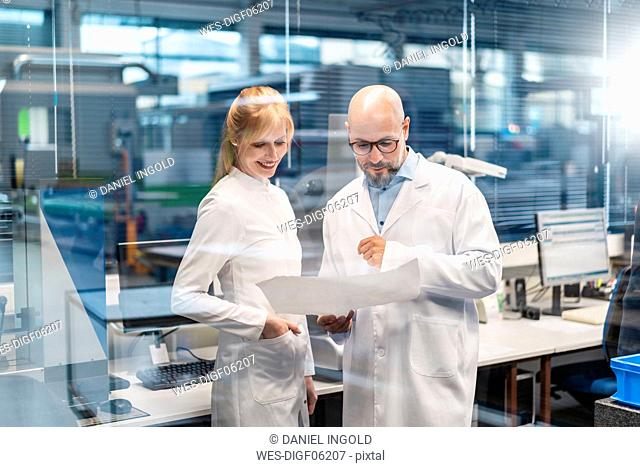 Two technicians wearing lab coats looking at plan