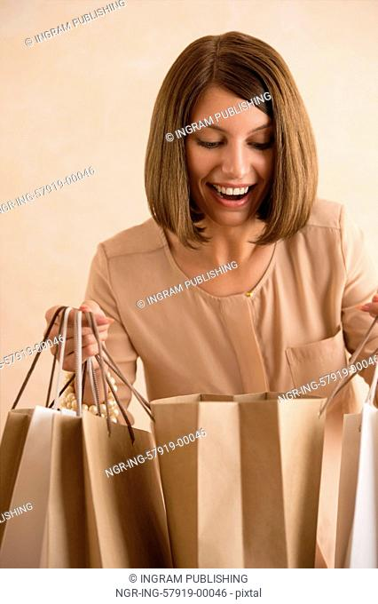Portrait of happy smiling woman holding shopping bags looking inside