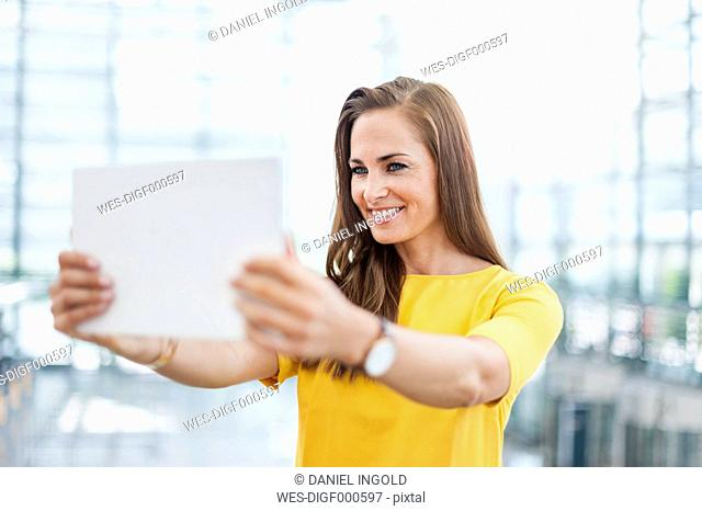 Smiling brunette woman holding digital tablet