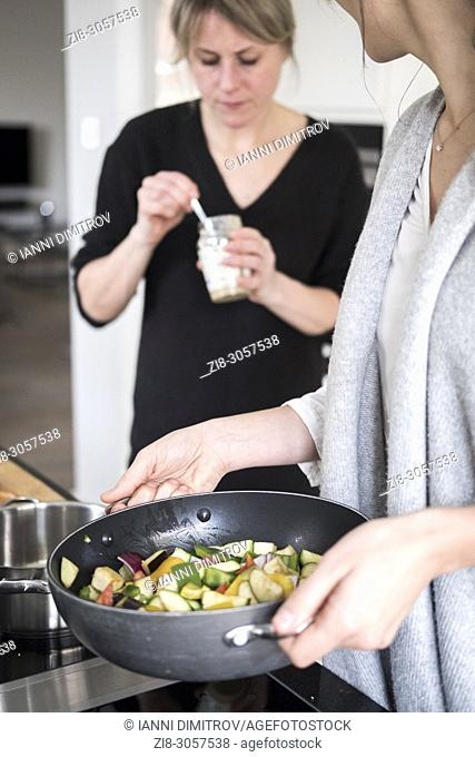 Friends cooking vegetarian food together