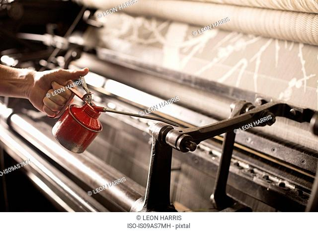 Hand of male weaver oiling old weaving machine in textile mill
