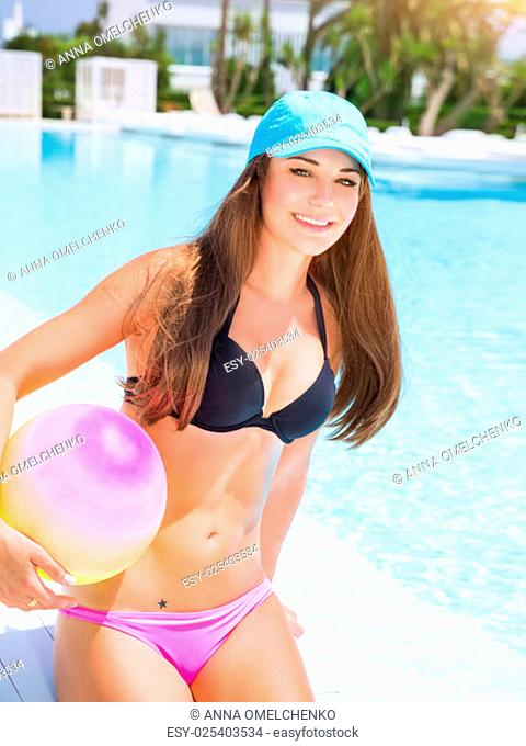 .Sexy sportive girl having fun in swimming pool with ball, enjoying luxury beach resort, active summer vacation, sport and enjoyment concept