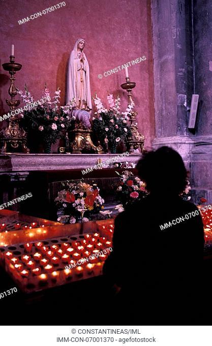 Baixa, Church of Sao Domingos, interior, woman lighting candle , Lisbon, Portugal, Europe