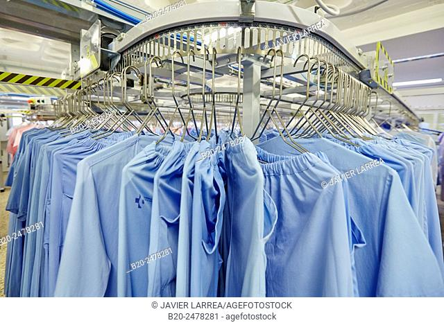 Scrubs hanging on rack in automated warehouse of hospital laundry, Hospital Donostia, San Sebastian, Basque Country, Spain