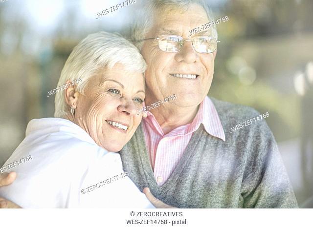 Portrait of smiling senior couple behind windowpane