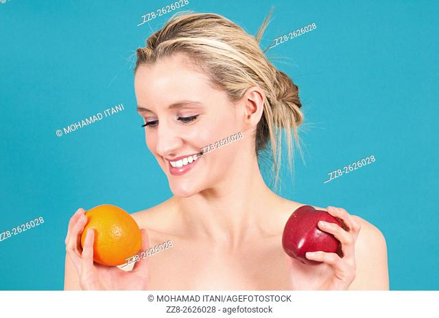 Young Caucasian woman comparing apple and orange fruits