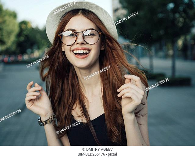 Wind blowing hair of laughing Caucasian woman