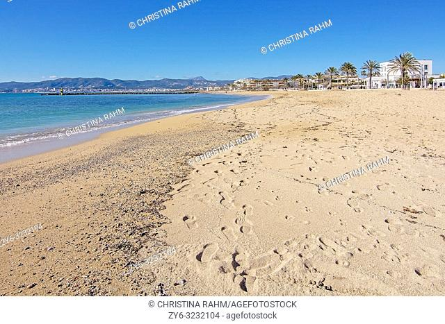PALMA DE MALLORCA, SPAIN - FEBRUARY 4, 2019: Empty sand beach in Ciudad Jardin and promenade with blue sky on a sunny day on February 4