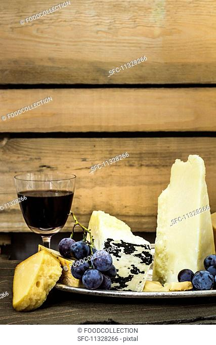 A cheese platter with grapes and a glass of red wine