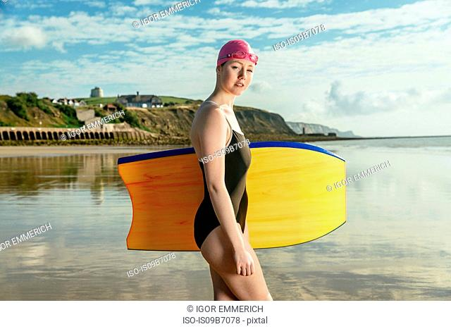 Young woman carrying surfboard on beach, Folkestone, UK