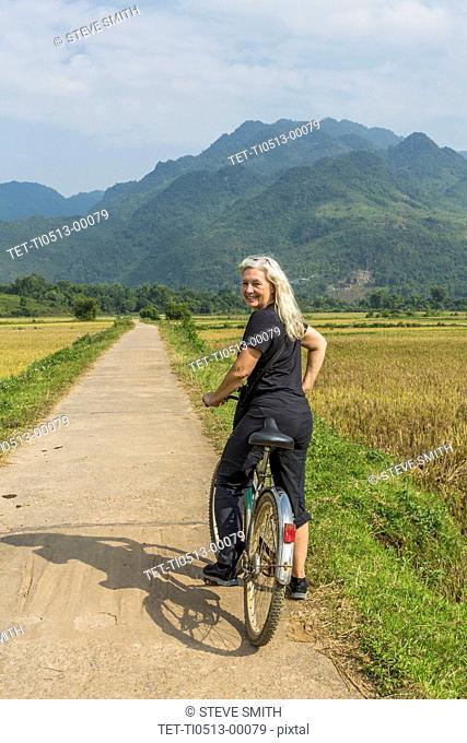 Woman bicycling in Mai Chau, Vietnam